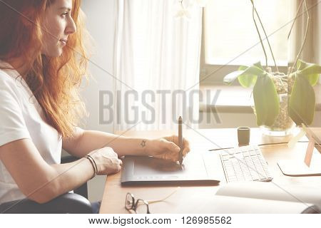 Cropped Side View Portrait Of Young Female Photographer Retouching Photos On Graphic Tablet In Front