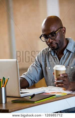 Graphic designer using laptop in office and holding a coffee in office