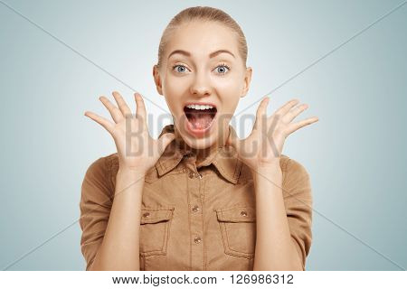 Portrait Of Blond Caucasian Girl Wearing Beige Shirt Screaming With Excitement And Joy.  Headshot Of