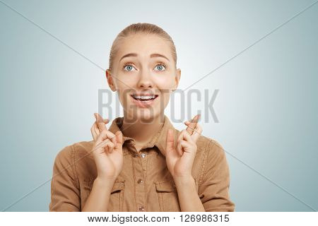 Fingers Crossed. Portrait Of Happy Young Woman Holding Her Fingers Crossed While Standing Isolated A