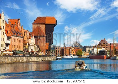 GDANSK, POLAND - APRIL 21, 2016: View of the riverside on Old Town by the Motlawa river in morning light. Old Town in Gdansk is a tourist attraction for visitors.