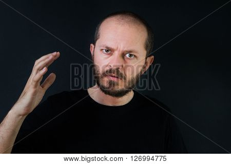 Aggressive man with beard and mustaches on black background in low key, holding hand and threatening, ready for fight