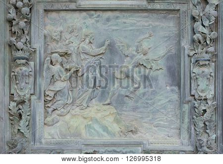PISA, ITALY - JUNE 06: Jesus Christ tempted by Devil in the desert, sculpture work from Giambologna's school, left portal of the Cathedral St. Mary of the Assumption in Pisa, Italy on June 06, 2015