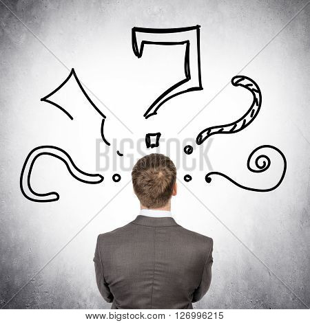 Rear view of businessman with big question marks on grey wall background