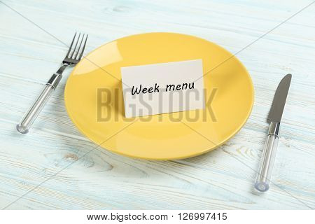 Yellow plate on a blue wooden table, week menu