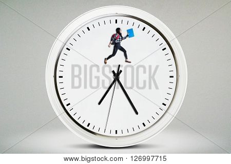 Image of a female college student jumping on a big clock. Concept of the time to back to school
