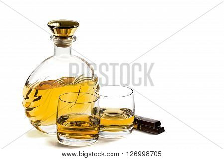 Bottle and two glass of whiskey with chocolate on white background ** Note: Visible grain at 100%, best at smaller sizes