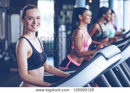 Spending great time at gym. Beautiful young cheerful woman in sportswear looking at camera with smile while running on treadmill at gym with other women