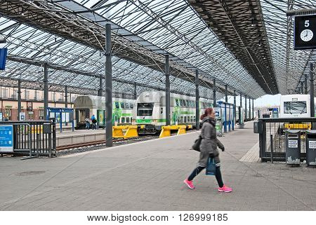 HELSINKI, FINLAND - APRIL 23, 2016: The Central Railway Station. People walk along the platform near the double decker trains (night trains).