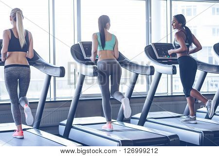Keep on running! Rear view of young beautiful women with perfect bodies looking at each other with smile while running on treadmill at gym