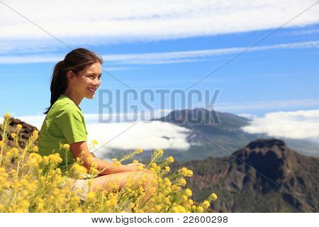 Hiker woman looking at view sitting on mountain top. Hiking on the peak of La Palma (Roque de los Muchachos), Canary Islands