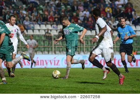 KAPOSVAR, HUNGARY - JULY 30: Benjamin Balazs (in green 18) in action at a Hungarian National Championship soccer game - Kaposvar (green) vs Videoton (white) on July 30, 2011 in Kaposvar, Hungary.