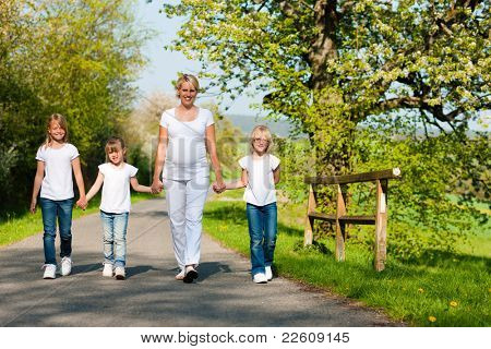 Kids and her mother walking down a path in spring, the mother is pregnant