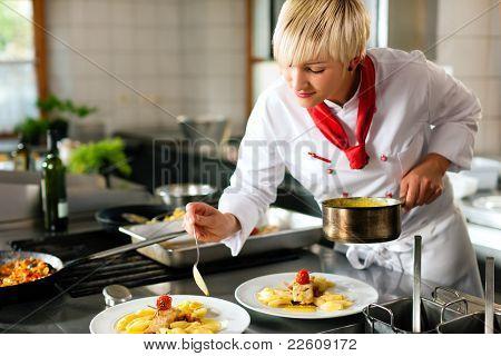 Weibliche Koch in einem Restaurant oder Hotel Küche kochen Köstlichkeiten, ist dekorieren sie die Gerichte