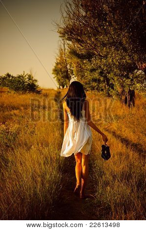 Barefoot Girl In White Dress With Shoes In Hand Is On The Field. Rear View