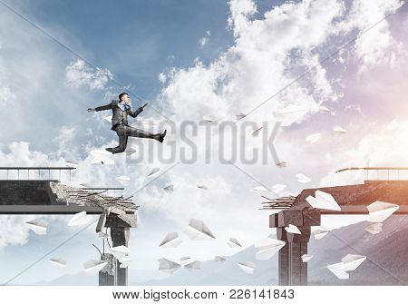 poster of Businessman Jumping Over Gap In Bridge Among Flying Paper Planes As Symbol Of Overcoming Challenges.