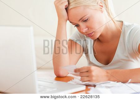 Stressed blond woman doing paperwork in her living room
