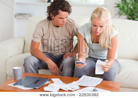 Shocked couple calculating their expenses in the living room