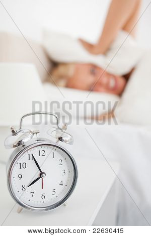 Portrait of a woman hiding her head in a pillow while the alarm clock is ringing in her bedroom