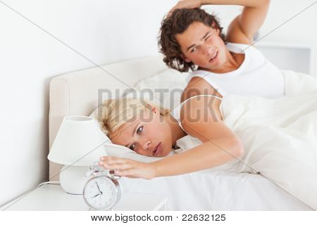 Tired couple waking up in their bedroom