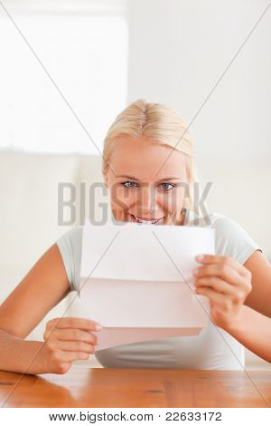 Smiling woman reading a letter in her living room