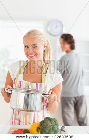 Portrait of a woman posing with a boiler while her fiance is washing the dishes in their kitchen