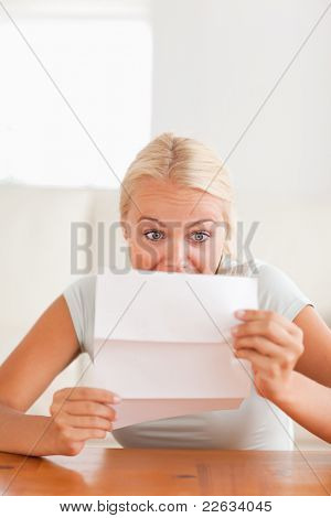 Woman looking at a letter in disbelief in her living room