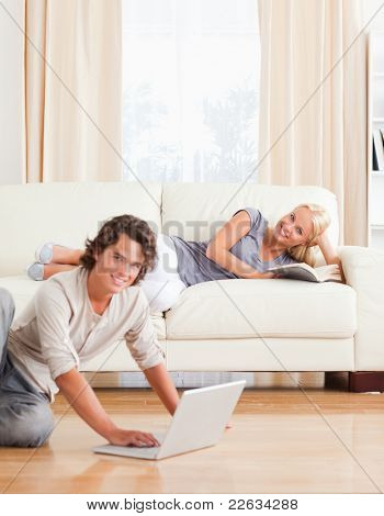 Portrait of a man with a laptop while his girlfriend is with a book looking at the camera