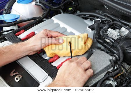 Mechanic holding a dip stick checking the engine oil on a v6 sports car