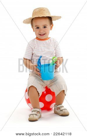 Little Boy Sitting On Dotted Ball, Holding Sandbox Toys