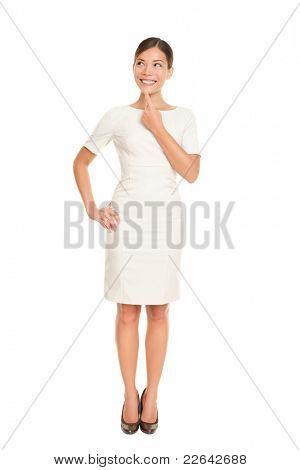 Thinking business woman standing in full body isolated on white background contemplating looking up to the side smiling happy. Beautiful Asian / Caucasian businessowman in dress suit.