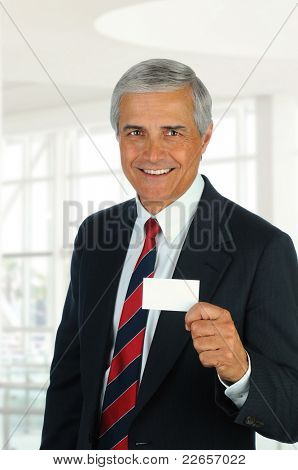 Smiling middle aged businessman in modern office setting holding out blank business card. Vertical Format.