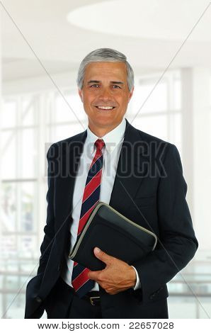 Smiling middle aged businessman in modern office setting holding a small binder. Vertical Format.
