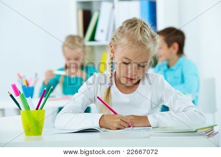 Portrait of lovely girl drawing with classmates on background