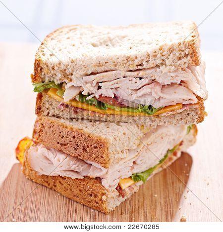 a turkey club sandwich cut in halves with selective focus