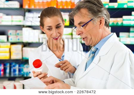 Two pharmacists with pharmaceuticals in hand consulting each other in a pharmacy