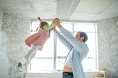 Dad Plays With His Little Daughter. The Man Lifts The Baby By The Handles. In His Eyes, Love And Ten poster