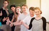 School class teacher and students stand in front of a blackboard with math work in a classroom durin poster