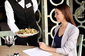 Waiter serving tasty salad at restaurant poster