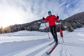 Cross-country skiing. Young man and woman doing outdoor exercise. Winter sport and healthy lifestyle poster