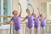 Young Ballerinas Rehearsing In Ballet Class. Group Of Young Ballerinas Performing Different Choreogr poster