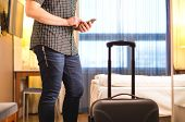 Man Using Smartphone In Hotel Room With Baggage And Suitcase. Tourist With Mobile Phone In Holiday R poster