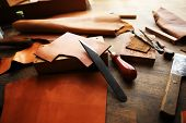 Leather craft or leather working. beautifully colored tanned leather on leather craftmans work desk poster