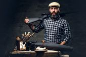 Studio Portrait Of A Bearded Traditional Hunter With His Trophy Holds A Rifle. poster