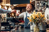 Positive Bearded Barista Male Selling Coffee To A Consumer In A Coffee Shop. poster