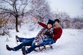 Lovely Couple Enjoy A Sleigh Ride. Lovely Couple Sledding. Funny Couple Play Outdoors In Snow. Happy poster