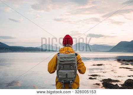 poster of Back View Of Male Tourist With Rucksack Standing On Coast In Front Of Great Mountain Massif While Jo