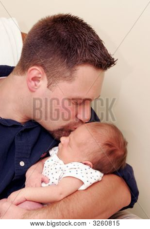 Man Kissing Newborn Baby