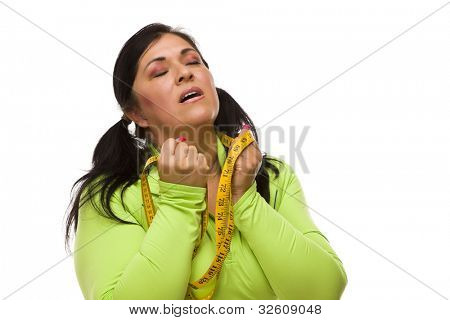 Attractive Frustrated Hispanic Woman with Tape Measure Against a White Background.