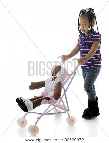 "A serious preschooler pushing her ""baby"" in a doll-sized umbrella stroller.  On a white background."